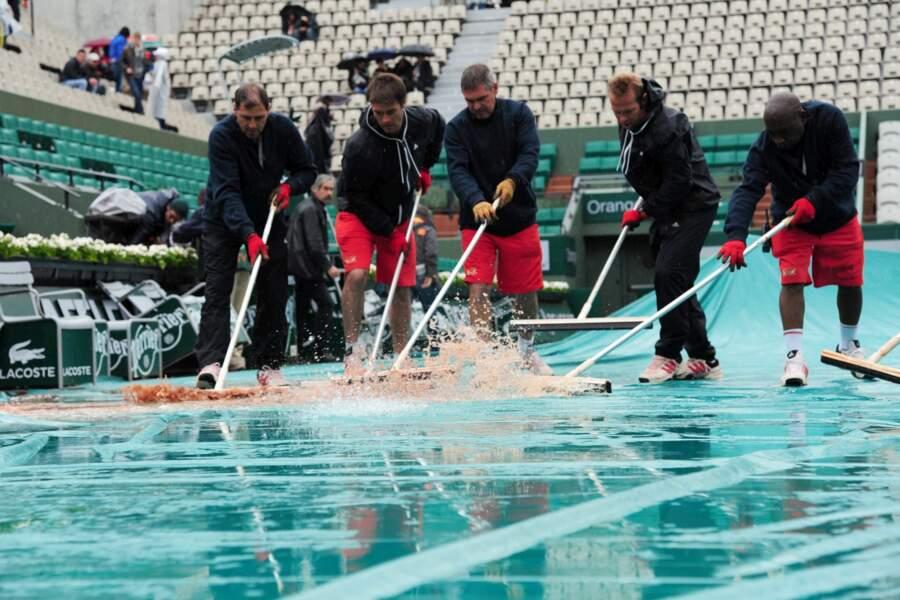 Entre les gouttes, le personnel de Roland Garros retire l'eau des bâches.