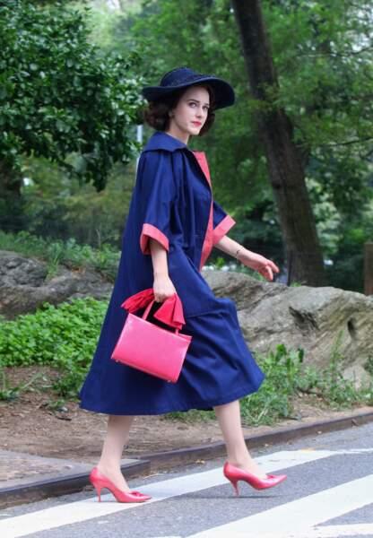 Accessoires roses et manteau bleu, l'héroïne avance d'un pas décidé